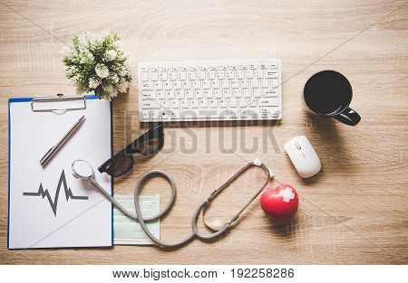 The doctor with a medical stethoscope check heart near a laptop on a wooden table
