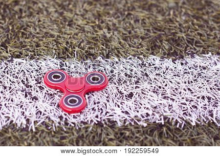 Top view of the popular spinner on a white strip on a green artificial turf football field
