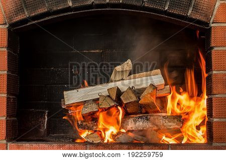 Firewood for coals burn out in the brazier. fire burning charcoal background barbeque grill