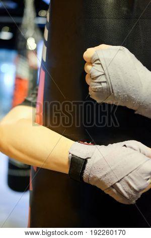 Close up of boxing glove hug sandbag