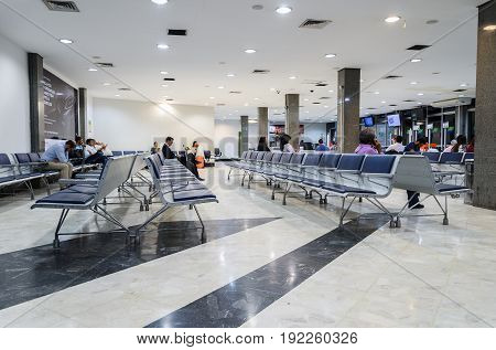 People Waiting For Departure And Some Empty Chairs On Departure Lounge