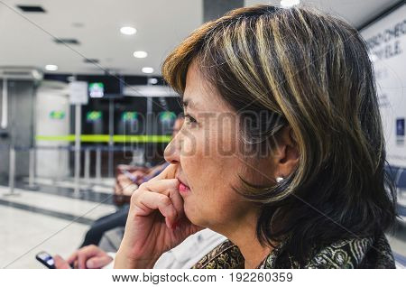 Close up on a woman waiting anxious on the airport's departure lounge.