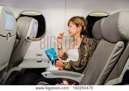 MATO GROSSO DO SUL BRAZIL - JUNE 15 2017: Woman eating some snacks and watching tv on a flight of Azul Airlines sitting during the flight.