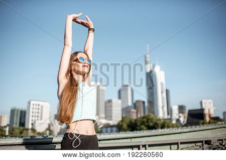 Young woman in sportswear stretching up on the beautiful modern city background in Frankfurt