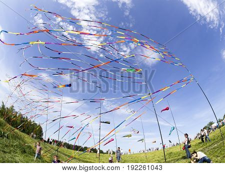 MOSCOW, RUSSIA - JUN 1, 2014: Fluttering in the wind colorful ribbons and colorful kites at the festival of kites with happy people and children around in Moscow Russia.