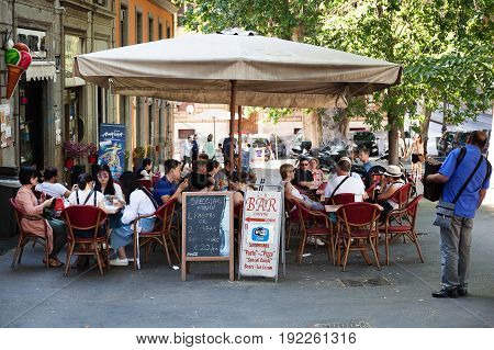 Rome Italy - June 9 2017: Some tourists sitting at the tables at a bar in Esquiline Square. An accordion player entertains people with his music.