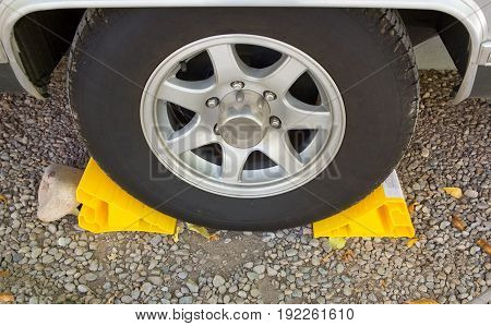 Yellow wheel chock or wheel stopper with wheel