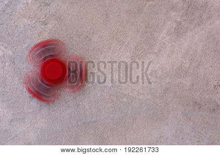 Red fidget spinner in motion stress relieving toy on concrete background.
