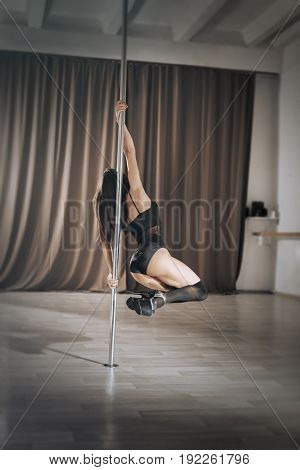 The girl is doing the exercises on the pylon by holding both hands by the pipe and rotating around it. Young pole dance woman upside down in dance hall.