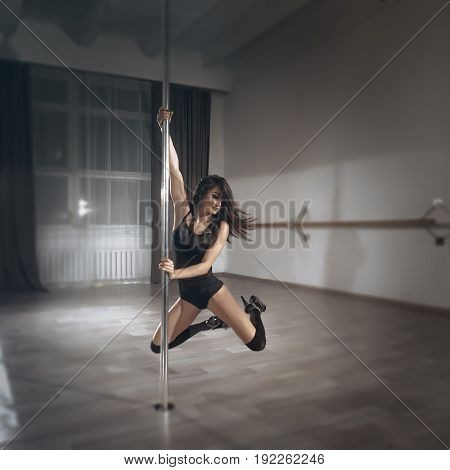 A girl performs exercises on a pylon.Pole dance woman on the pylon.