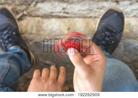 Closeup of a young caucasian man playing with a red fidget spinner on a concrete background. Popular spinner gadget in 2017.