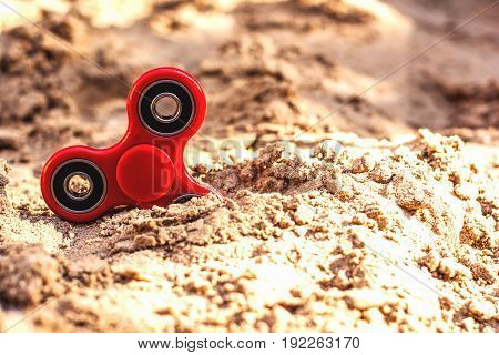 Popular spinner gadget in 2017 against the background of sand. Modern red plastic spinner fidget game for young people. Learn spinning tricksimprove concentration.