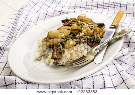 vegetarian dish grilled mushroom with rice andthyme on a plate