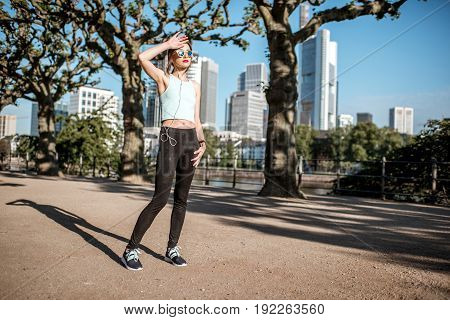 Young tired woman in sportswear having a morning exercise in the park with skyscrapers on the background in Frankfurt city