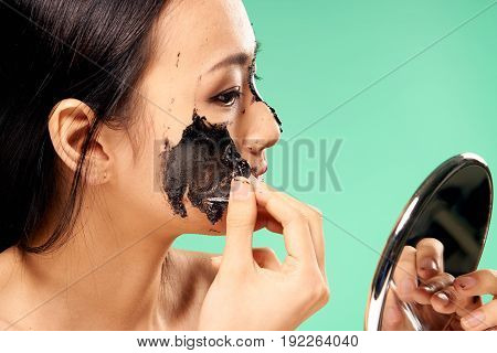 Cosmetic face mask, Asian. Girl on a green background, coal face mask.