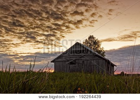 An old abandoned barn house in the midsummer night at the rural Finland. The sun is not setting it's just going down to horizon and getting back up.