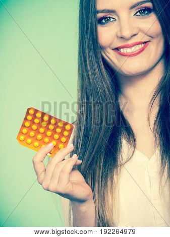 Woman holding pills blister pack vitamin c in hand synthetic way of health care. Studio shot on green background