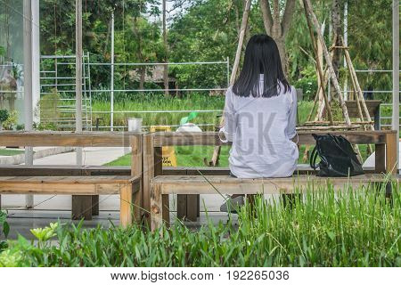 Relaxation Concept : Back view woman sitting relax on wooden chair at outdoor garden surrounded green natural.