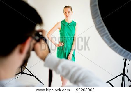 Male photographer working with model at his studio