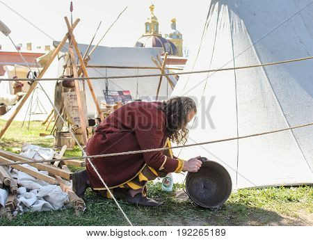 St. Petersburg Russia - 28 May, The man is cleaning the dishes, 28 May, 2017. Festival of the Legends of the Norwegian Vikings in St. Petersburg.