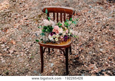 Gorgeous wedding bouquet on an old brown chair standing outside in park.