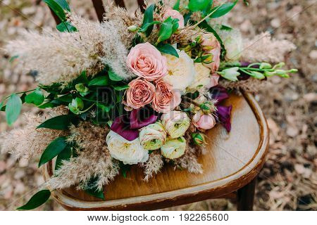 Beautiful wedding bouquet on an old brown chair standing outside in park. Close up