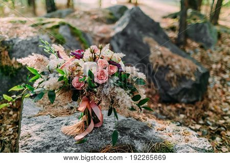Beautiful wedding bouquet lying on a stone in the park. Autumn wedding. Outside