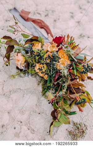 Beautiful wedding bouquet consisting of different flowers lying on a stone in the park. Bunch of flowers. Close-up