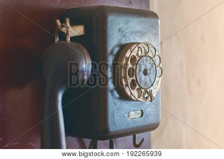 Black old fashioned rotary dial phone hanging on the wall