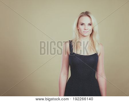 Summer trendy fashionable outfit ideas concept. Blonde attractive woman wearing short blue cocktail dress.