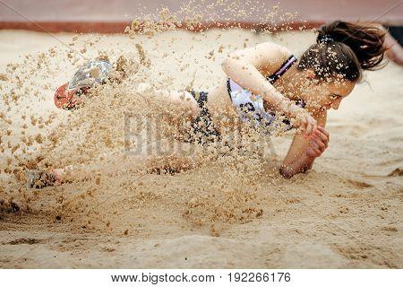 Chelyabinsk Russia - June 4 2017: women jumper landing in sand long jump during UrFO Championship in athletics