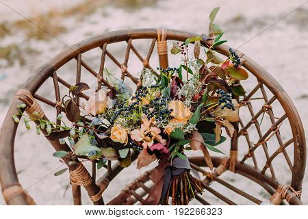 Beautiful bridal bouquet consisting of different flowers lying on an old brown chair. Bunch of flowers. Close-up
