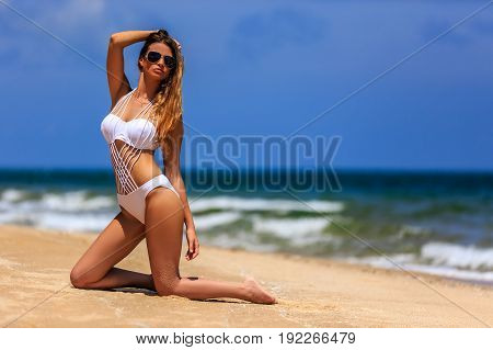 Model In White Bikini Posing At The Beach