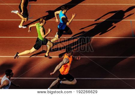 Chelyabinsk Russia - June 4 2017: shadow runners men running sprint race at stadium during UrFO Championship in athletics