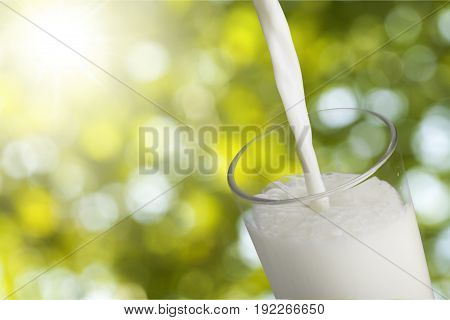 Glass pouring milk green white background sky