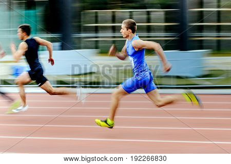 Chelyabinsk Russia - June 4 2017: blurred motion two sprinters runners men run race in 200 meters during UrFO Championship in athletics