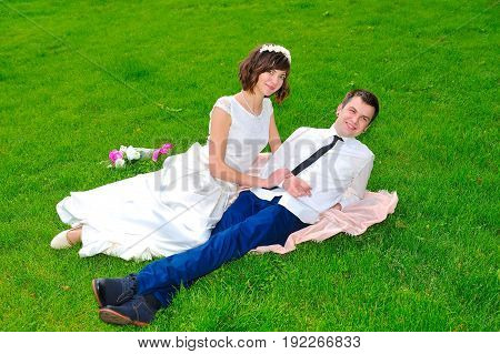 Young And Handsome Newlyweds Lie On The Green Lawn