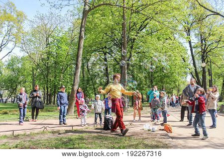 St. Petersburg Russia - 28 May, Performance of the artist with soap bubbles, 28 May, 2017. People at an entertainment event in a city park.