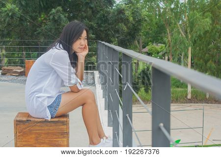 Portrait Asian woman sitting on wooden chair at flat top of the roof buildings, relaxing and looking forward.