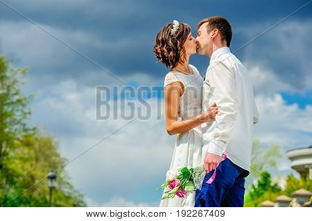 Young And Handsome Newlyweds On A Walk In The Park: The Kiss