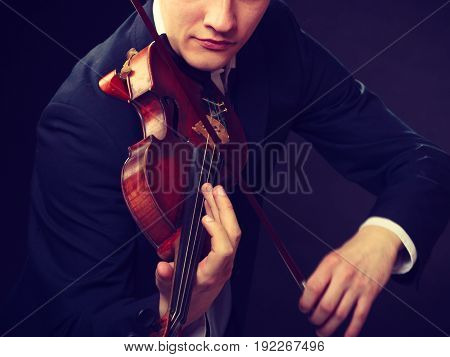 Music passion hobby concept. Close up young man man dressed elegantly playing emotionally on wooden violin. Studio shot on dark background