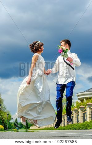 Young And Handsome Newlyweds On A Walk In The Park. Jump Into Happiness