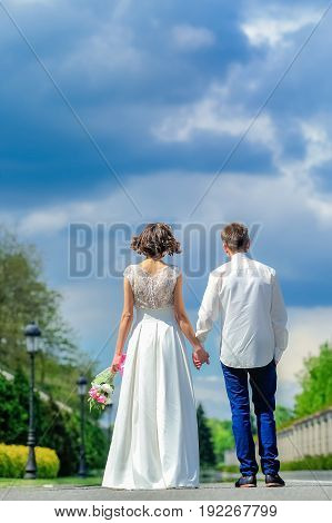 Young And Handsome Newlyweds On A Walk In The Park
