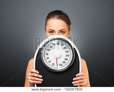 Young woman scales hiding background view beautiful