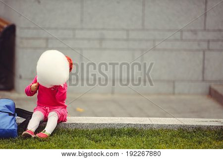 Little girl with sweet cotton wool sitting outside on the lawn