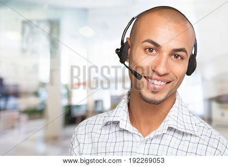 Smiling portrait of afro american man wearing a headset on a white background with copy space. Telemarketer.