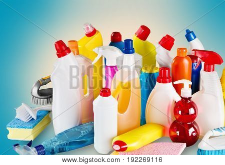 Many plastic cleaning bottles, supplies and sponges.