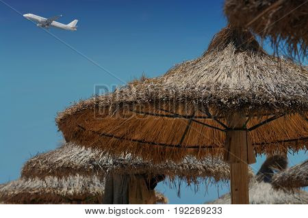 Parasol made of straw in the cloudless blue sky a passenger plane.