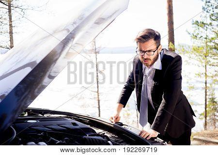 Man standing in front of his broken car