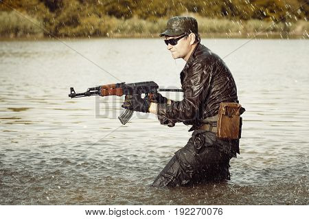 Soldier in uniform attacking in lake with assault rifle